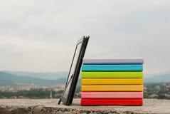 Pile de livres colorés avec le reade d'e-livre Photos libres de droits