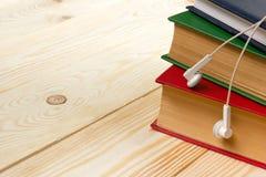 Pile de livres colorés sur la table et les écouteurs en bois Concept d'Audiobook Photographie stock libre de droits