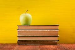 Pile de livres de livre cartonné, de journal intime sur la table en bois de plate-forme et de fond jaune De nouveau à l'école Cop Photo libre de droits