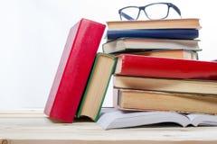 Pile de livres et de verre sur la table en bois d'isolement sur le fond blanc De nouveau à l'école Copiez l'espace Photos stock