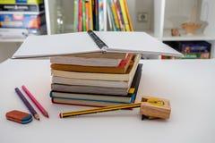 Pile de livres et de papeterie sur le fond blanc Faire le travail images stock
