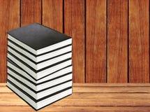 Pile de livres sur la table en bois au-dessus du fond en bois Images libres de droits