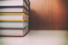 Pile de livres sur le bureau avec le filtre de vintage Images stock
