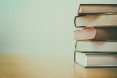 Pile de livres sur le bureau avec le fond de tache floue de filtre de vintage Photo stock