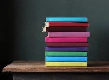 Pile de manuels dans la couverture colorée sur la table Photos libres de droits