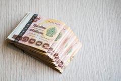 Pile de mille argents thaïlandais de bain sur la table en bois Photographie stock