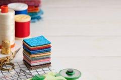 Pile de morceaux carrés de tissus colorés, accessoires pour piquer image stock