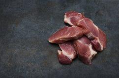 Pile de morceaux de viande frais sur la table foncée photos stock