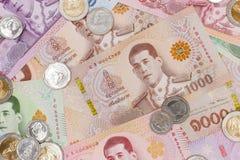 Pile de nouveaux billets de banque et de pièces de monnaie de baht thaïlandais images stock