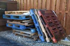 Pile de palettes en bois multicolores de chariot élévateur près de décharge image stock
