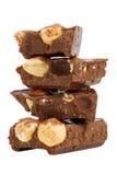 Pile de parties de chocolat avec des noisettes Images libres de droits