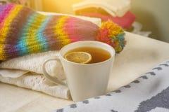 Pile de photo de fond d'hiver des vêtements de laine chauds sur la table, une tasse de thé chaud Images stock