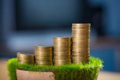 Pile de pièce d'or sur l'herbe artificielle dans le pot, sur la table en bois Images stock