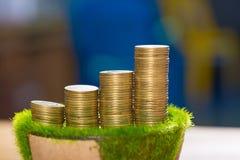 Pile de pièce d'or sur l'herbe artificielle dans le pot, sur la table en bois Photographie stock libre de droits