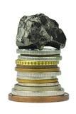 Pile de pièce de monnaie avec du charbon sur le dessus Photos libres de droits