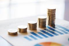 Pile de pièces de monnaie dans une rangée sur le graphique de gestion Photo stock