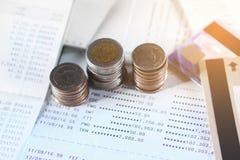 Pile de pièces de monnaie sur le compte d'économie avec la carte de crédit photos stock