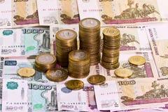 Pile de pièces de monnaie sur le fond de billets de banque Images stock