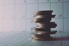 Pile de pièces de monnaie sur le calendrier de livre et de tache floue Images stock