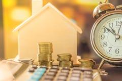 Pile de pièces de monnaie surfaçant pour acheter à la maison avec le modèle d'horloge et de maison photographie stock