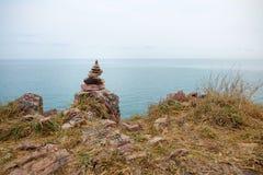 Pile de pierre d'équilibre sur le cliffside avec le fond de paysage marin Photographie stock libre de droits