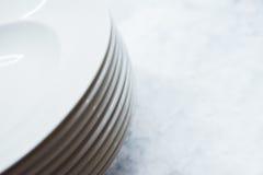 Pile de plats propres sur la table Nettoyez les plats préparés sur une table blanche dans la cuisine Image stock
