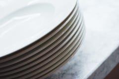 Pile de plats propres sur la table Nettoyez les plats préparés sur une table blanche dans la cuisine Photo libre de droits