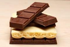 Pile de quatre plans rapprochés noirs et un blancs de chocolat Photo stock