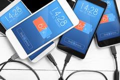 Pile de smartphones reliés à la source d'énergie Concept de bas b Images stock