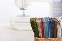 Pile de tissus piquants colorés dans le panier sur le fond de la machine à coudre image libre de droits