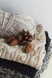 Pile de vêtements chauds des tricots tricotés avec des cônes de pin plus de Image stock