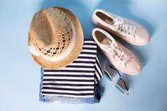 Pile de vêtements et d'accessoires d'été de dames Combinaisons de jeans, verres, espadrilles, chapeau en osier, dessus rayé V?tem image stock