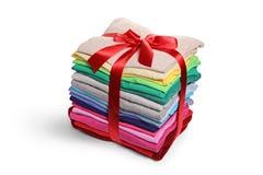 Pile de vêtements repassés et emballés enveloppés avec un ruban rouge As Images stock