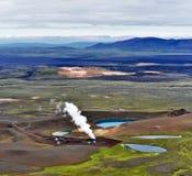 Pile de vapeur et parties actives de la centrale géothermique de Krafla prochaine par le cratère de volcan avec le lac Krafla Vit photographie stock libre de droits