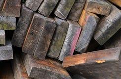 Pile de vieux conseils survivant au grunge en bois couvert foncé de fond de matériaux de construction d'épave de mousse images libres de droits