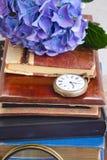 Pile de vieux livres avec les fleurs et l'horloge Image libre de droits