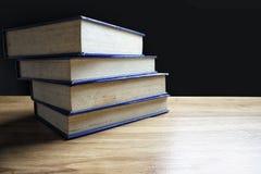 Pile de vieux livres sur le bureau avec un fond noir Image libre de droits