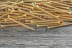 Pile de vis de cuivre sur le conseil en bois photo libre de droits