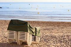 Pile of deck chairs on the sea beach. Pile of deck chairs on the empty sea beach Royalty Free Stock Images