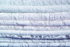 A pile of delicate traditional lace textile fabrics with a natural pattern of white and blue. stock image