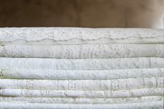 A pile of delicate traditional lace textile fabrics in a natural pattern in white color royalty free stock image