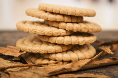 Pile of delicious vanilla cookies surrounded by. Cinnamon sticks on wooden table Stock Images