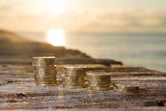 Pile della moneta di libbra con il tramonto sui soldi del molo Immagini Stock