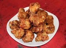 Pile des ailes de poulet frit croustillantes dans le plat blanc sur la table en bois rouge image stock
