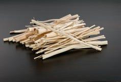 Pile des bâtons en bois secs sans écorce sur le fond foncé Photos stock