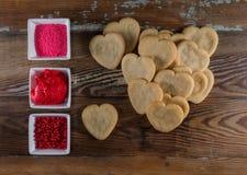Pile des biscuits de coeur avec des cuvettes de décorations Photographie stock libre de droits