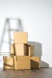 Pile des boîtes en carton sur le fond blanc avec l'ombre d'échelle Photo libre de droits