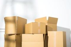 Pile des boîtes en carton sur le fond blanc avec l'ombre d'échelle Image libre de droits