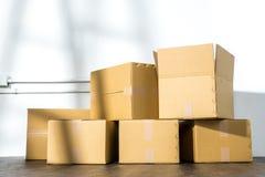 Pile des boîtes en carton sur le fond blanc avec l'ombre d'échelle Photo stock