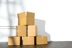 Pile des boîtes en carton sur le fond blanc avec l'ombre d'échelle Images stock